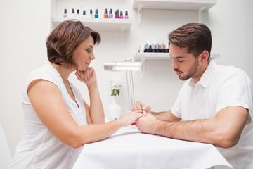 Manicurist giving customer a manicure