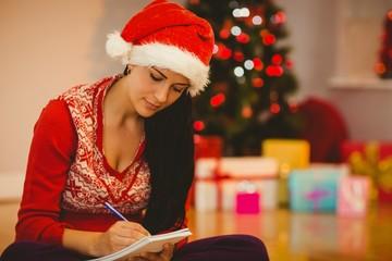 Festive brunette writing her list
