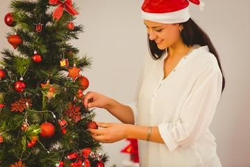 Woman hanging christmas decorations on tree