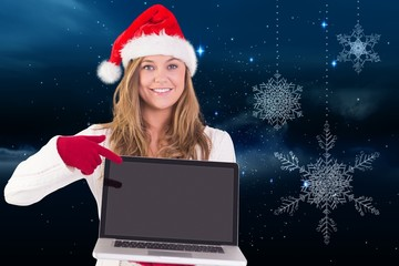 Composite image of festive blonde pointing to laptop