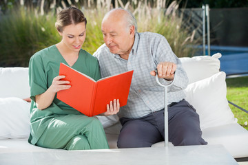 Senior Man Reading Book With Female Caretaker On Couch