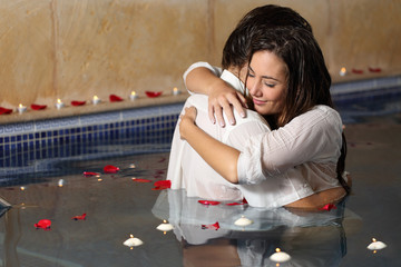 Romantic couple hugging in a pool  with candles and rose petals