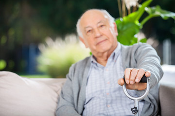 Portrait Of Senior Man Holding Metal Cane