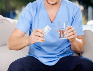 Male Caretaker Holding Blister Pack And Glass Of Water