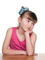 Haughty little girl at a school desk
