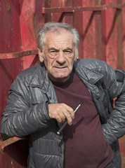 handsome old italian man smoking an electronic cigarette