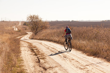 Woman riding a mountain bike on a rural  road, back view.