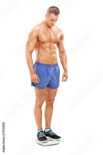 canvas print picture Handsome shirtless man standing on a weight scale