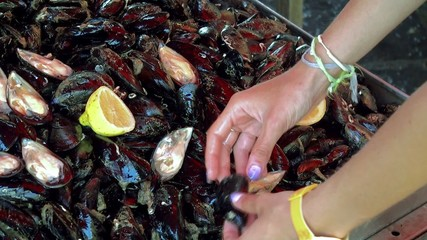 Buyer of fresh mussels at the Catania fish market.  Sicily