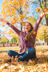Happy Woman Sitting on Ground Playing Dry Leaves
