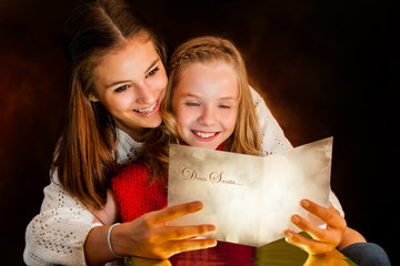 Girl reading Christmas card to sister.