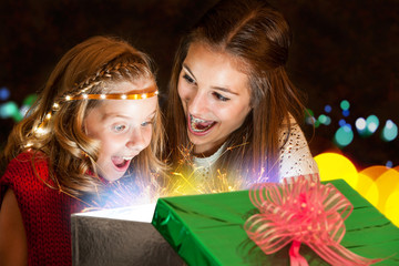 Girls opening present with great expectation.