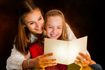 Woman reading Christmas card to youngster.