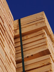 Stacks of planks against the deep blue sky