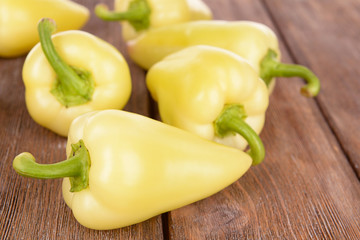 Yellow peppers on wooden background