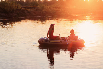 happy couple in boat at sunset