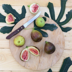 Figs with fig's leaves on the wooden board