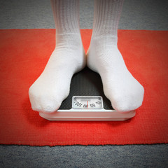 Overweight man standing on a retro style weighing machine