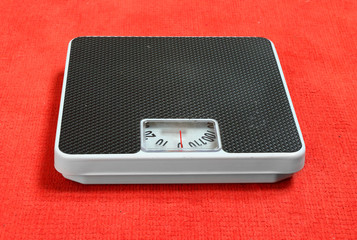 Retro style weighing machine on a pink background.