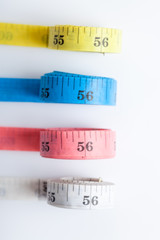 four rolls of colorful measuring tapes