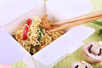 Chinese noodles in takeaway box on fabric background