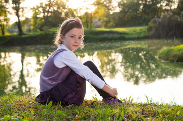 Little girl relax and sitting in park at lake