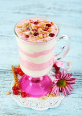 Cranberry milk dessert in glass, on color wooden background