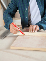 Carpenter Marking On Wood With Pencil