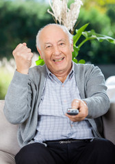 Cheerful Senior Man Clenching Fist While Using Remote Control