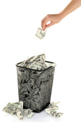 Hand throwing money into trash can isolated on white