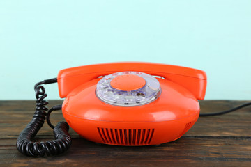 Old red disk phone on wooden table on blue background