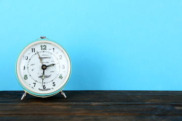 Old alarm clock on wooden table on blue background