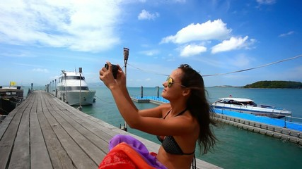 Woman in glasses photographs selfie on the bridge Koh Samui