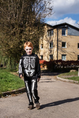 Little red haired boy wearing halloween skeleton costume