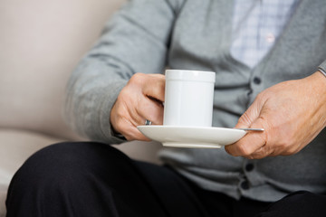 Midsection Of Senior Man Holding Coffee Cup On Couch