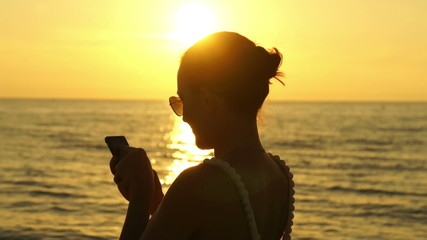 Woman texting a message on the beach at sunset