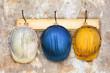 Leinwanddruck Bild - Three construction helmets hanging on a hat-rack