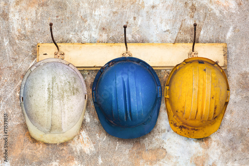 Three construction helmets hanging on a hat-rack - 71539851