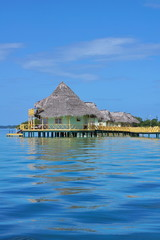 Caribbean resort over water with thatched bungalow