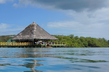 Caribbean restaurant over water with thatched roof