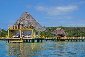 Over water bungalow with thatch roof Caribbean sea
