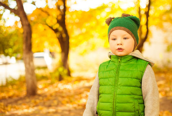 boy in green jacket at fall background