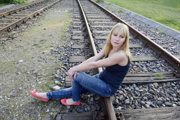 Frau sitzt auf Schiene