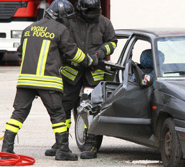 Firefighters open the door of the car with a pneumatic shears