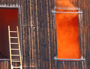 Orange smoke comes out of the window and a ladder of the fire ne