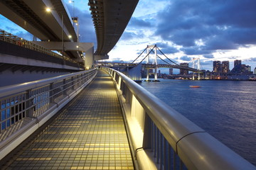 Tokyo bay and rainbow bridge at sunset time from walking across