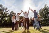 Group of friends at the park holding hands and rise up