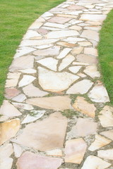 Natural brown stone pathway and green grass
