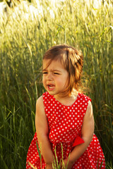 cute little girl in red dress is crying