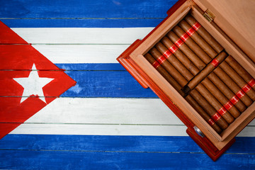 Humidor with cigars over Cuban flag background